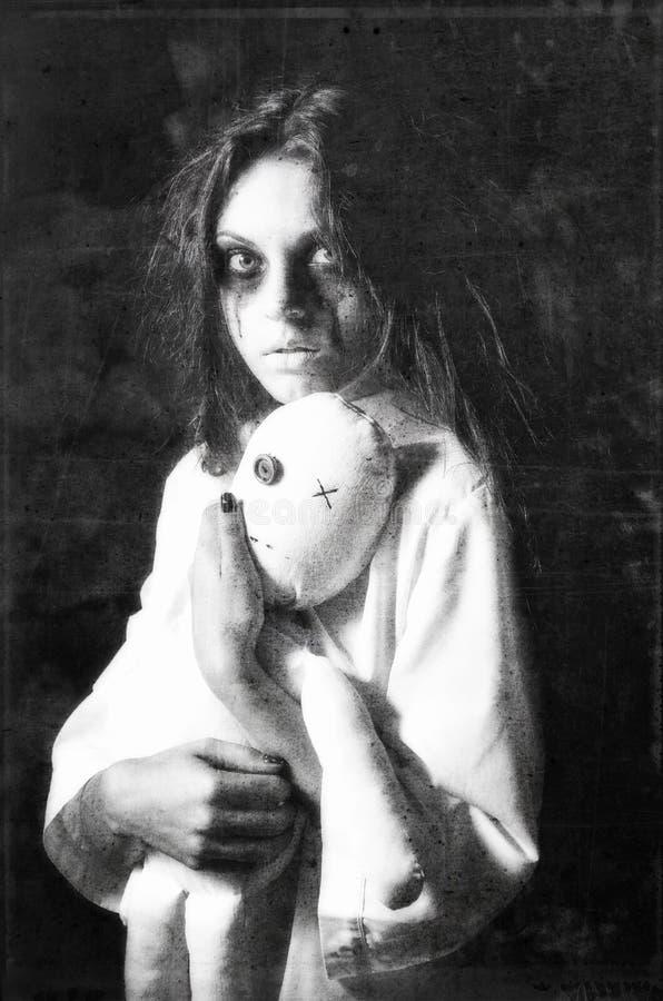 Skjuten fasastil: mystisk spökeflicka med moppetdockan i händer Grungetextureffekt royaltyfri bild
