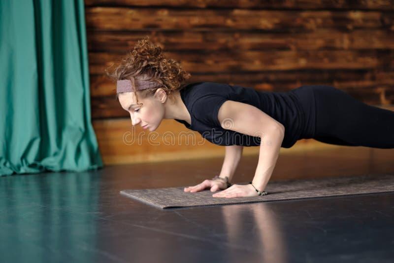 Skjuter övande yoga för kvinnan som gör ups, press ups, chaturangadandasanaen poserar royaltyfria foton