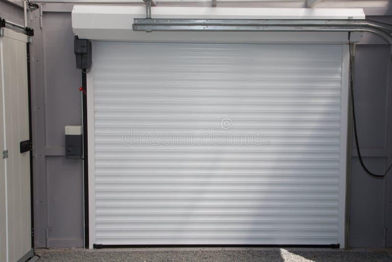 Skjuter den kommersiella garageporten för automatisk elektrisk rulle-upp upp dörr i modernt byggande hus arkivbilder