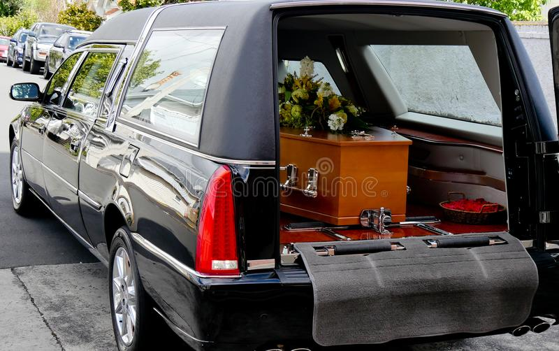 Skjutit av en färgrik casket i en likvagn eller kapell för begravning eller jordfästning på kyrkogården arkivbilder