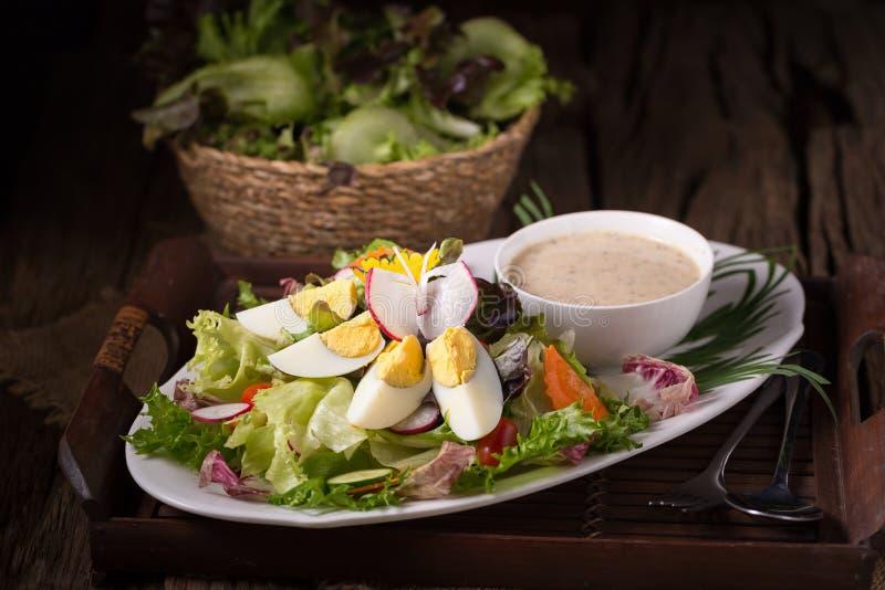 Skjutit av grön sallad med rädisan och det hårdkokta ägget på vita plommoner royaltyfri foto