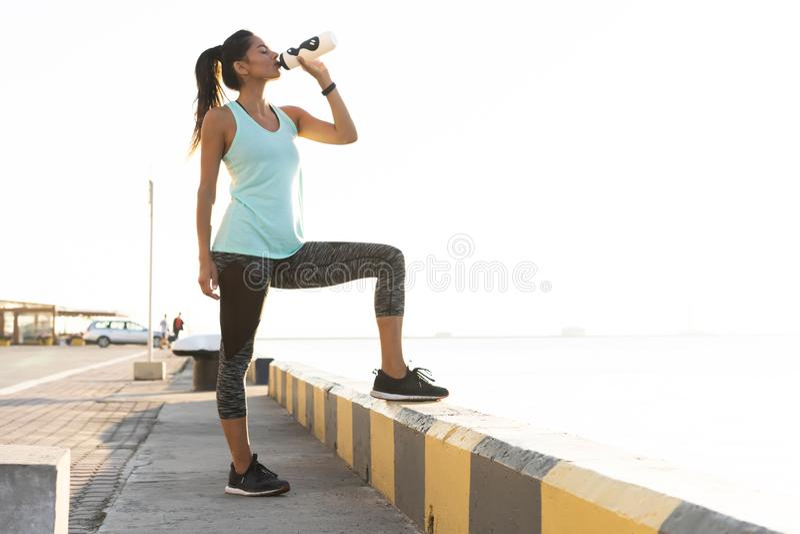 Skjutit av stående det fria för härlig kvinnlig löpare som rymmer vattenflaskan Konditionkvinna som tar ett avbrott, når att ha k arkivfoton