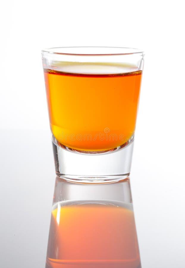 Skjutit av whisky i litet exponeringsglas royaltyfria foton