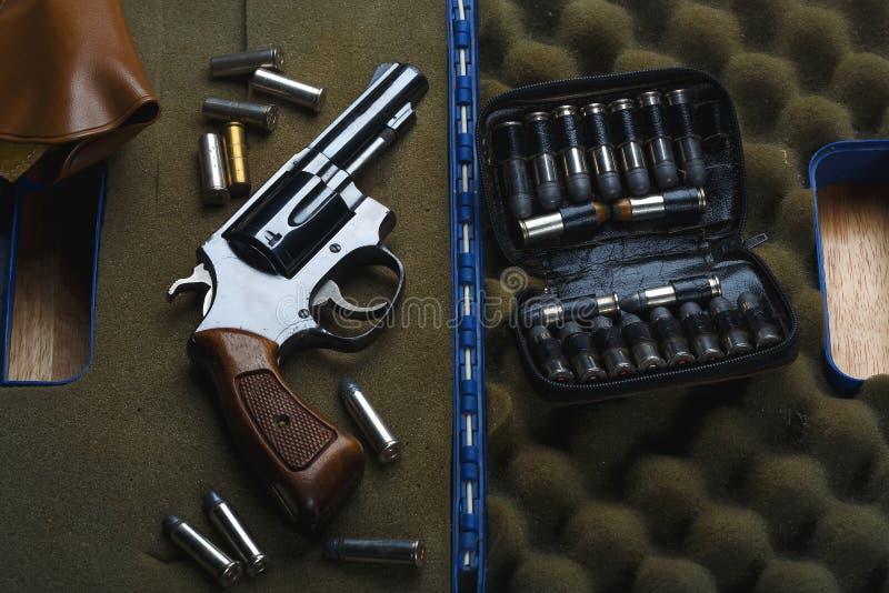 Skjutvapenrevolver, gammal revolver, 38 vapen och ammunitionar, döljer vapnet med begrepp för kulhemskydd arkivbild