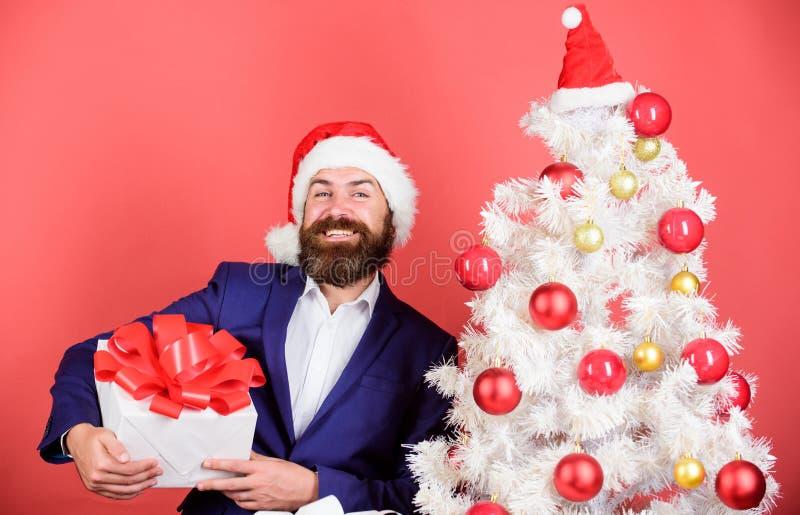 Sklep z prezentami Przyjęcie świąteczne Człowiek brodaty hipster formalny strój bożonarodzeniowy drzewo do trzymania pudełka upom obraz royalty free