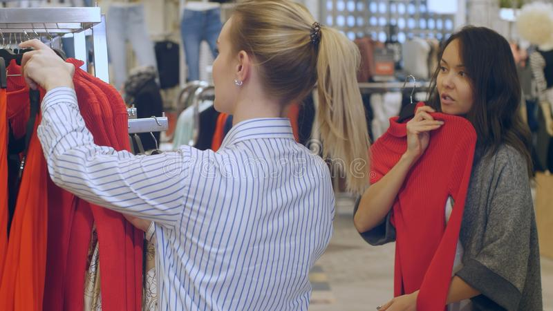 Sklepowego asystenta pomocy młoda kobieta shoose suknia w centrum handlowym obrazy stock