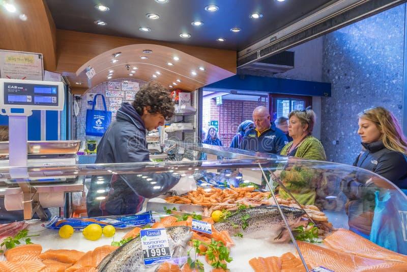 Sklepowego asystenta porci klienci w owoce morza robią zakupy w Melbourne obraz stock