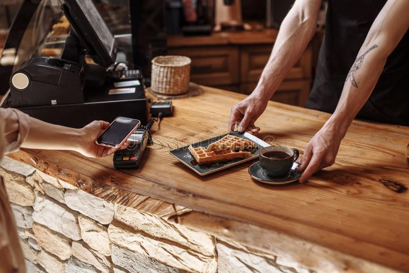 Sklepowy asystent oferuje czarną kawę z ciastkami zdjęcia stock