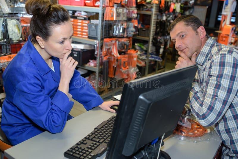 Sklepowy asystent patrzeje dla części zapasowych przy magazynowym komputerem osobistym zdjęcia stock