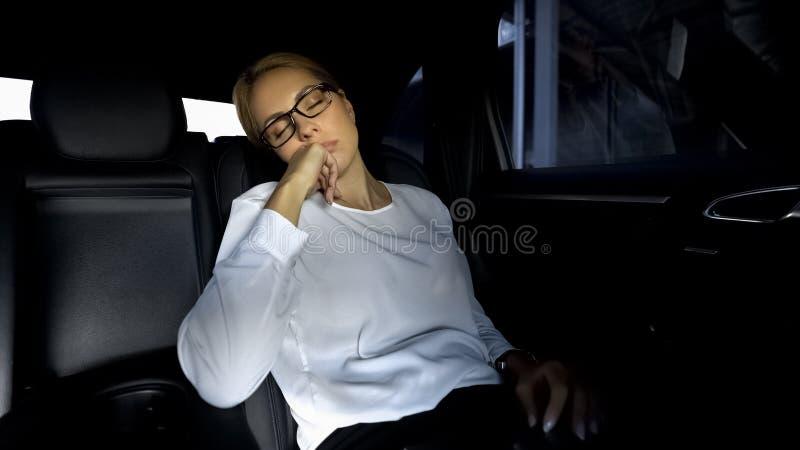 Skołowana kobieta przysypia na tylnym siedzeniu samochód, iść opóźniony spotkanie z partnerami obrazy stock
