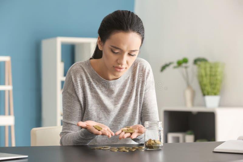 Skołatane młodej kobiety liczenia monety przy stołem zdjęcie royalty free