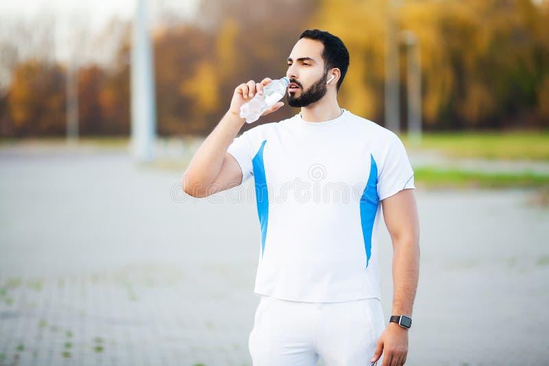 Skołowana biegacza mężczyzny napoju woda na parku po treningu zdjęcie stock