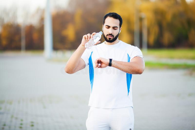Skołowana biegacza mężczyzny napoju woda na parku po treningu obrazy royalty free