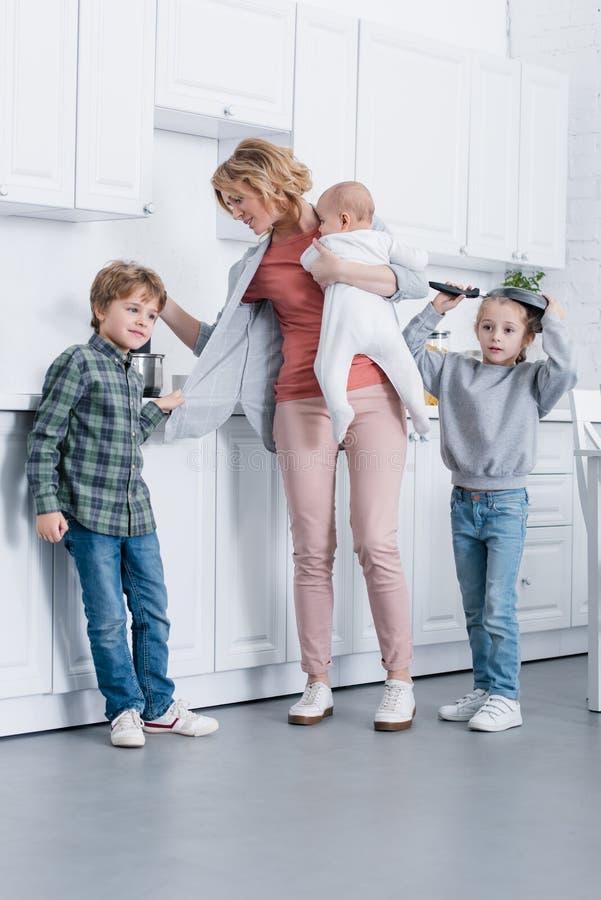skołowana matka z dziecięcym dzieciaka kucharstwem podczas gdy niegrzeczny dzieci bawić się ilustracji