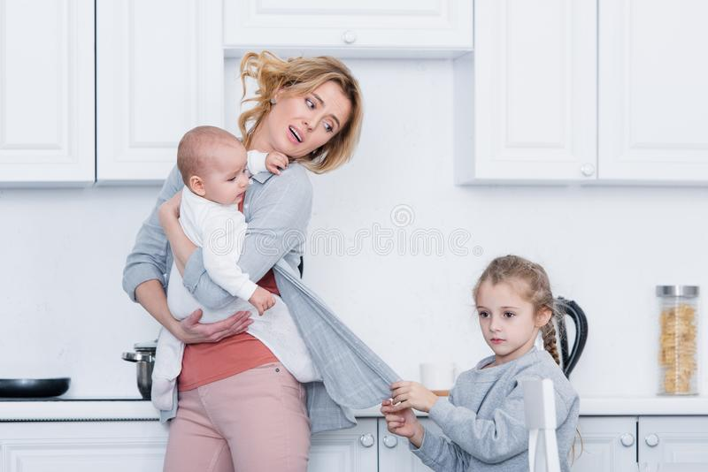 skołowanego macierzystego mienia dziecięcy dziecko podczas gdy niegrzeczna córka trzyma jej kardigan royalty ilustracja