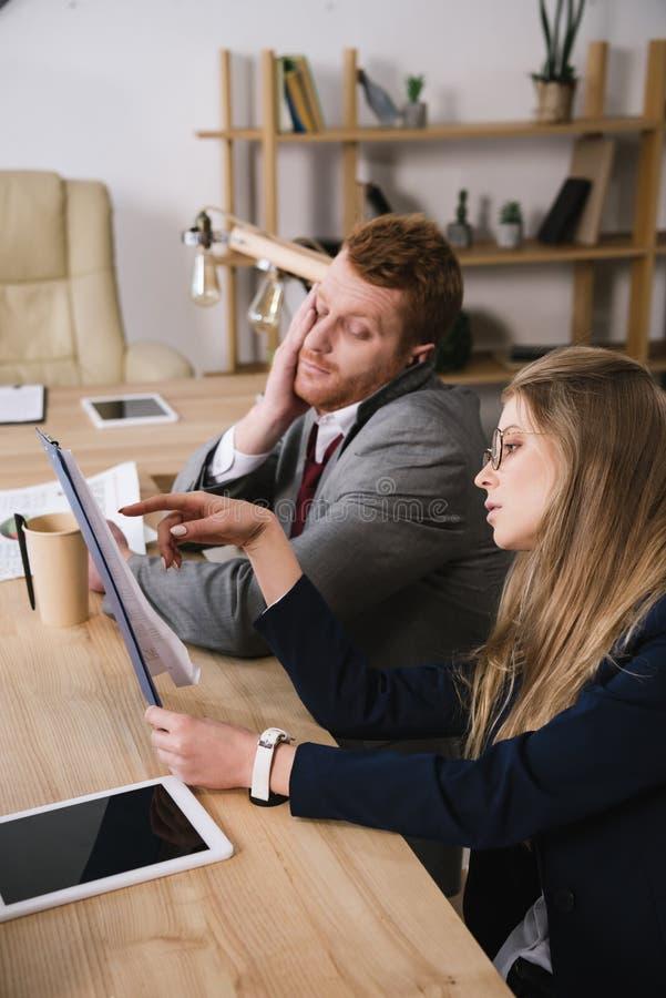 skołowani businesspartners patrzeje dokumenty wpólnie zdjęcia stock