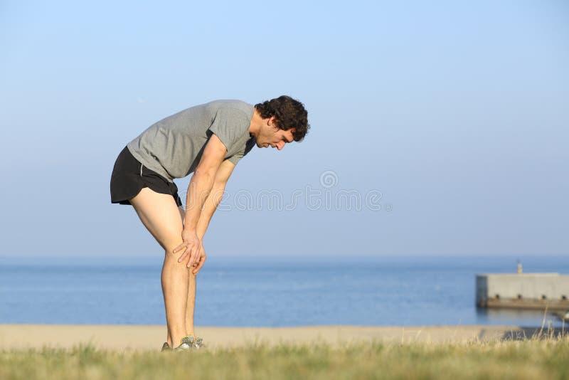 Skołowany biegacza mężczyzna odpoczywa po treningu obraz royalty free