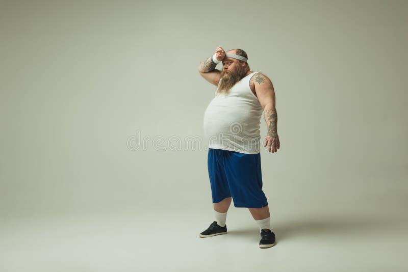 Skołowany gruby mężczyzna odpoczywa po biegać fotografia royalty free