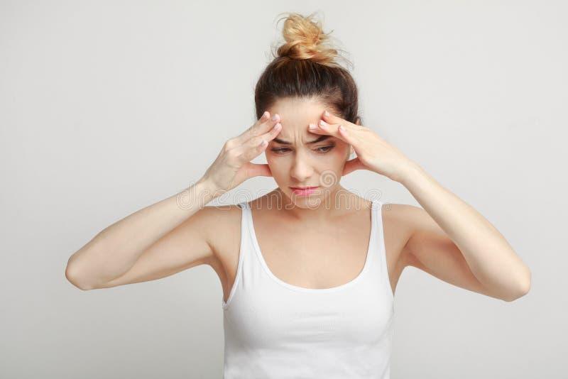 Skołowany kobiety cierpienie od migreny nad szarym tłem zdjęcie royalty free