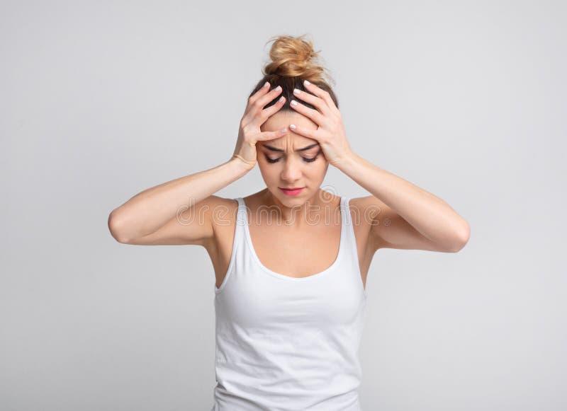 Skołowany kobiety cierpienie od nieznośnej migreny nad tłem obraz stock
