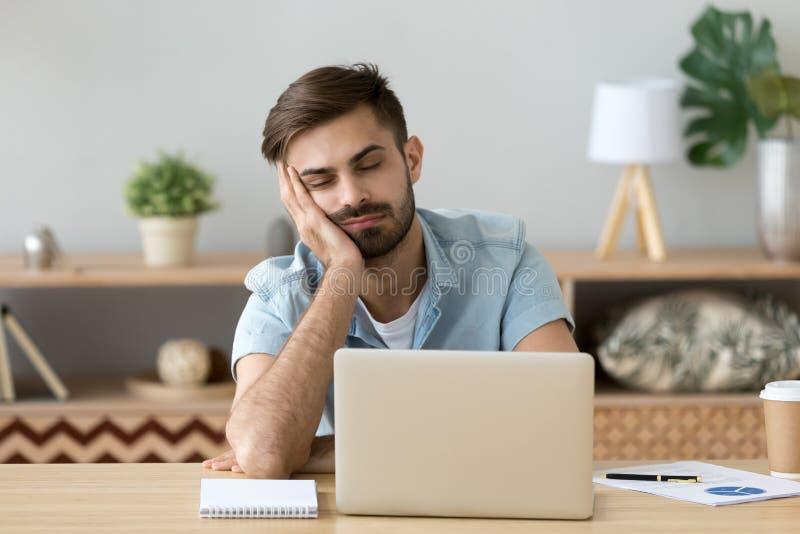 Skołowany mężczyzna spada uśpiona pobliska laptop miejsce pracy w domu obraz stock