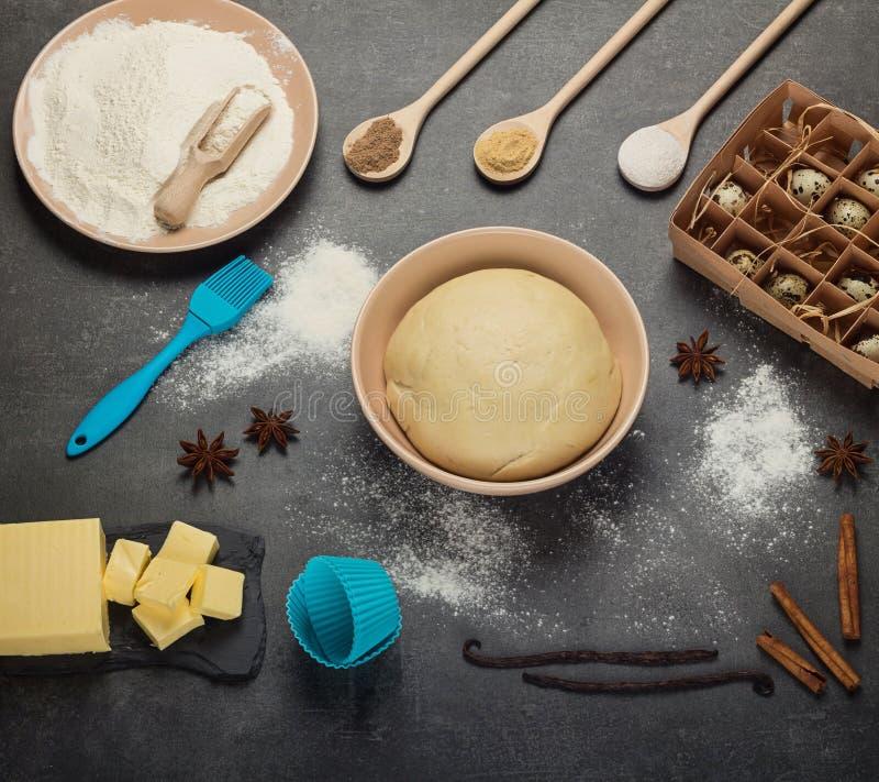 Skończony ciasto w pucharze, drewniane łyżki z pikantność, mąka i masło na szarość, ukazujemy się zdjęcia royalty free