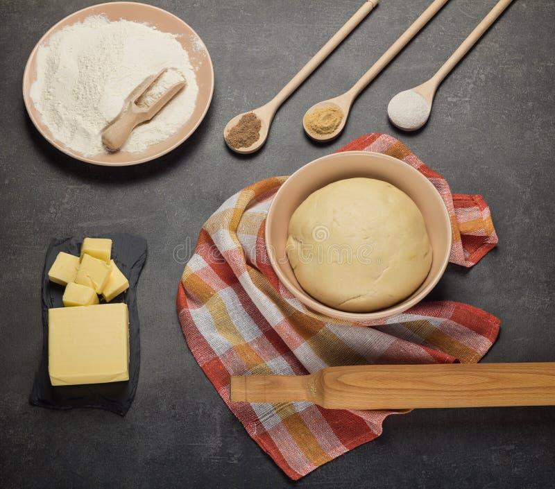 Skończony ciasto w pucharze na ręczniku, mące i maśle na szarość, zdjęcie stock