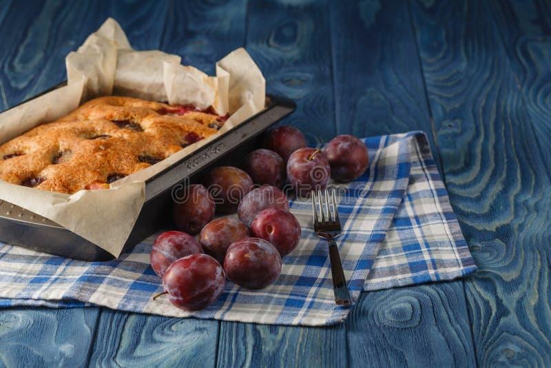 Skończony kulebiak pióropusze i brzoskwinie na drewnianym biurku błękitnym bac i zdjęcia stock