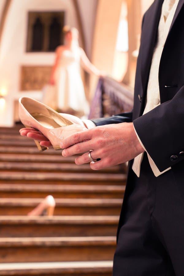 Sko för bröllop för ` s för brud för hand för brudgum` s hållande royaltyfria bilder