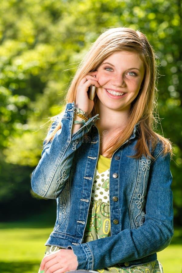 Skoczna młoda dziewczyna opowiada na jej telefonie fotografia royalty free