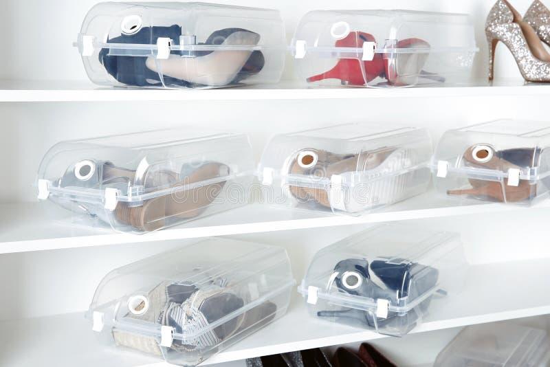 Skodon och plast- askar på hyllor i garderob Skolagring royaltyfri bild