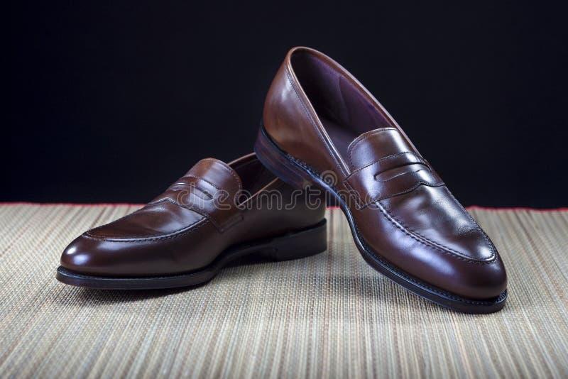Skodonbegrepp och idéer Par av stilfull dyr modern kalvläderbrunt Penny Loafers Shoes arkivfoton