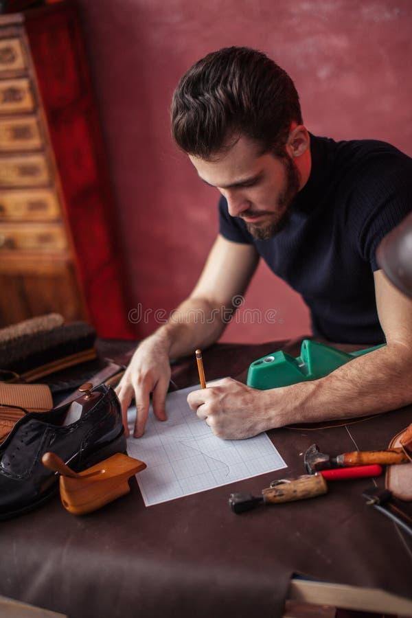 Skodonformgivare som sitter på tabellen och drar modellen royaltyfria foton