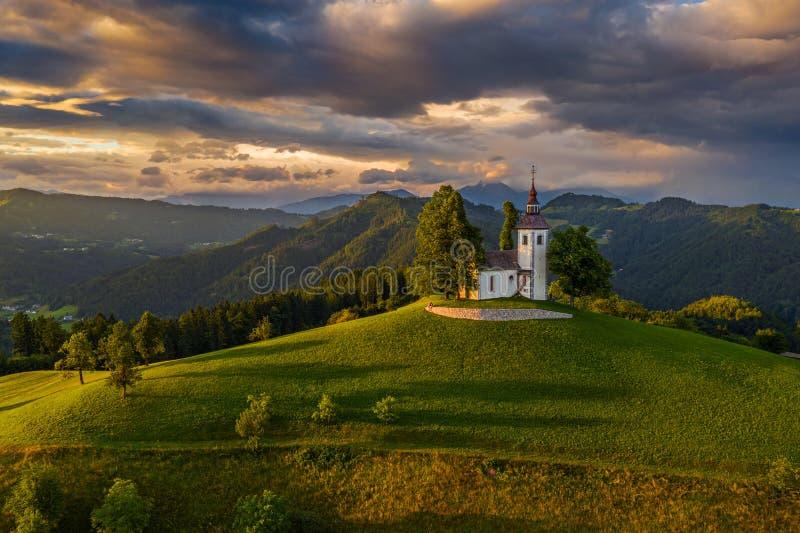 Skofja Loka, Словения - вид с воздуха красивой церков вершины холма Sveti Tomaz St. Thomas с изумительным красочным заходом солнц стоковая фотография