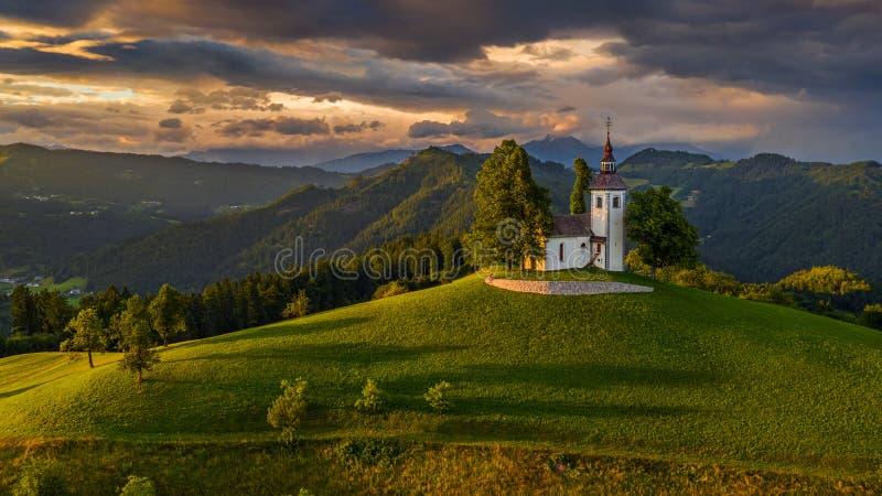 Skofja Loka, Словения - вид с воздуха красивой церков вершины холма Sveti Tomaz St. Thomas с изумительным красочным заходом солнц стоковое фото rf