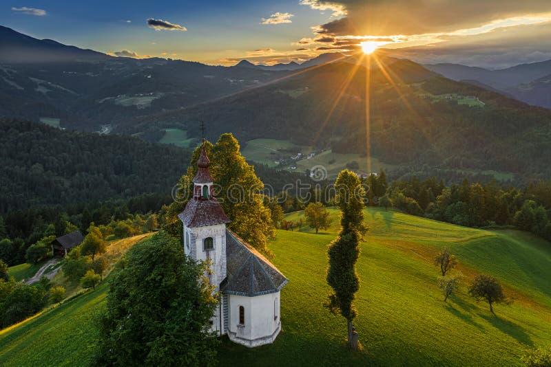 Skofja Loka, Словения - вид с воздуха красивой церков Sveti Tomaz St. Thomas вершины холма с изумительным заходом солнца стоковое изображение rf