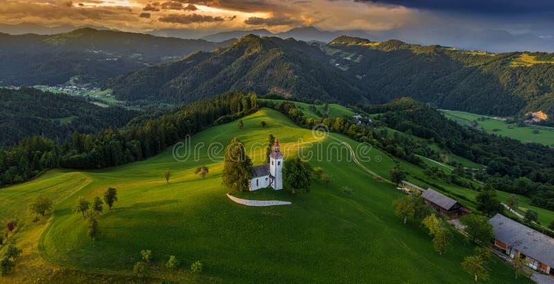 Skofja Loka, Словения - воздушный панорамный вид красивой церков вершины холма Sveti Tomaz St. Thomas с изумляя заходом солнца стоковое изображение rf
