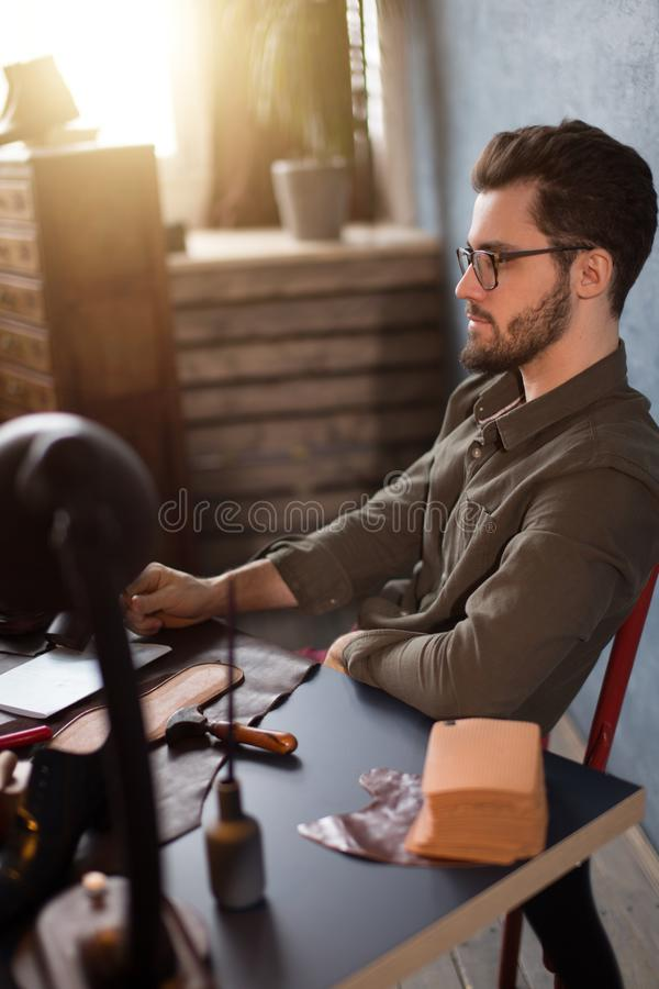 Skoformgivaren som har, vilar, medan sitta på arbetsplatsen arkivbild