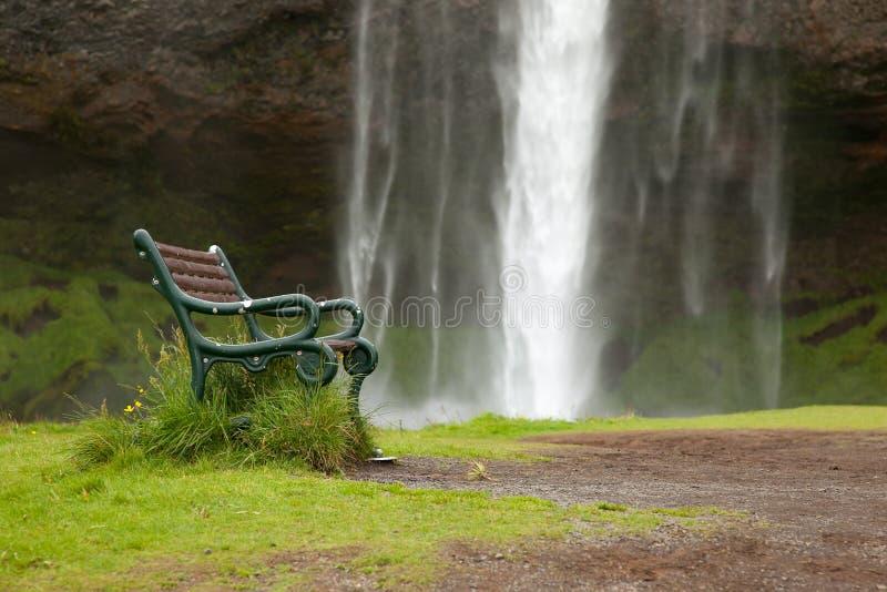 Skogafalls vattenfall nära mot bakgrunden av bänkar i Island Begreppet av stillhet arkivfoto