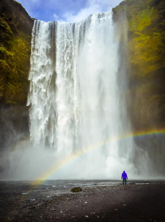 Skogafoss waterfall in Iceland. Man wit blue jacket looking at waterfall. Rainbow royalty free stock photos