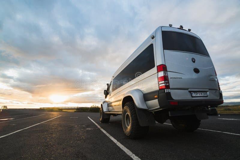 SKOGAR, ISLAND - AUGUST 2018: Superjeepbus mit großen Rädern auf der Straße während des Sonnenuntergangs in Island stockbild