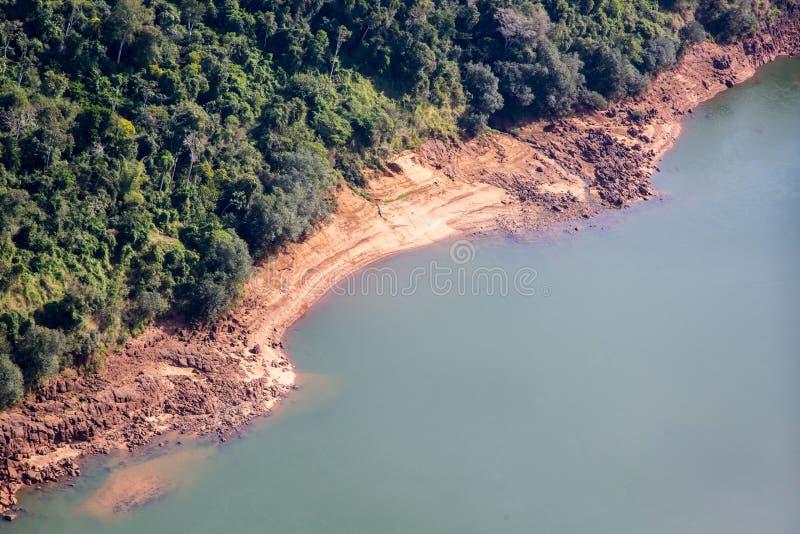 Skogar och lera och steniga banker av den flyg- sikten för Iguazu flod Gräns av Brasilien och Argentina härligt dimensionellt dia royaltyfri foto