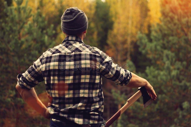 Skogsarbetare i rutig skjorta och yxa royaltyfri fotografi