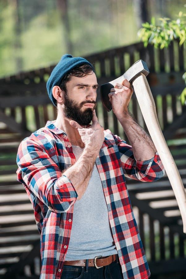 skogsarbetare i rutig skjorta som rakar skägget vid yxan royaltyfria foton