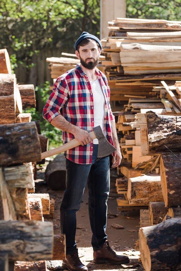 skogsarbetare i rutigt skjortaanseende med yxan mellan journaler arkivfoto
