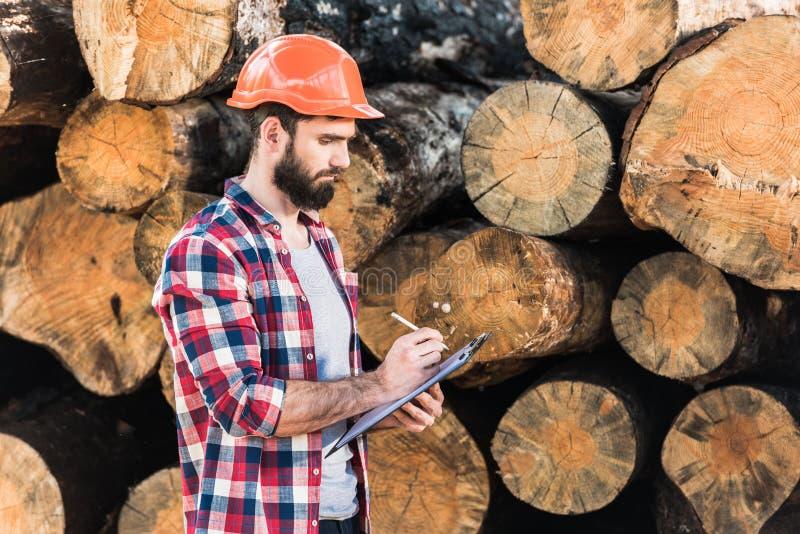 skogsarbetare i skyddande hjälmhandstil i skrivplatta på journaler royaltyfri foto