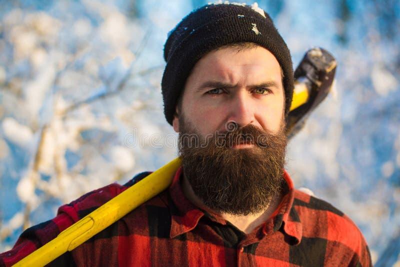 Skogsarbetare i träna med en yxa Brutal skäggig man med skägget och mustasch på vinterdag, stilig snöig skog arkivbilder