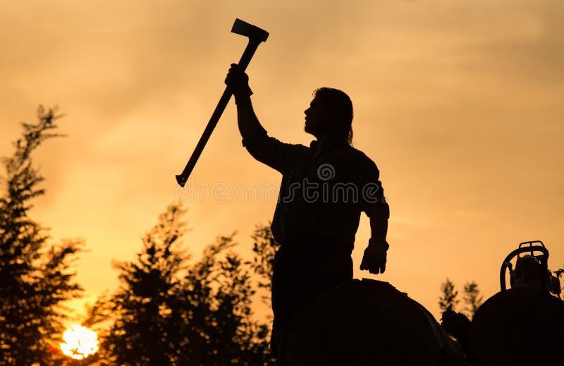 Skogsarbetare med yxa på solnedgången royaltyfri bild