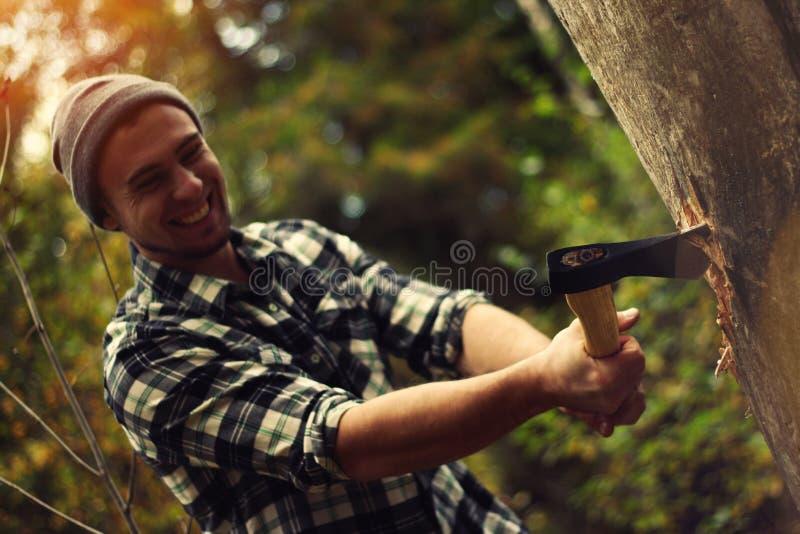 Skogsarbetare som hugger av en trädstam i skogen arkivbild