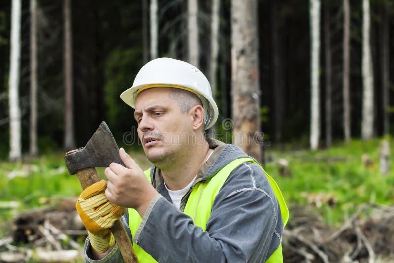 Skogsarbetare som kontrollerar yxaskärpa arkivfoto